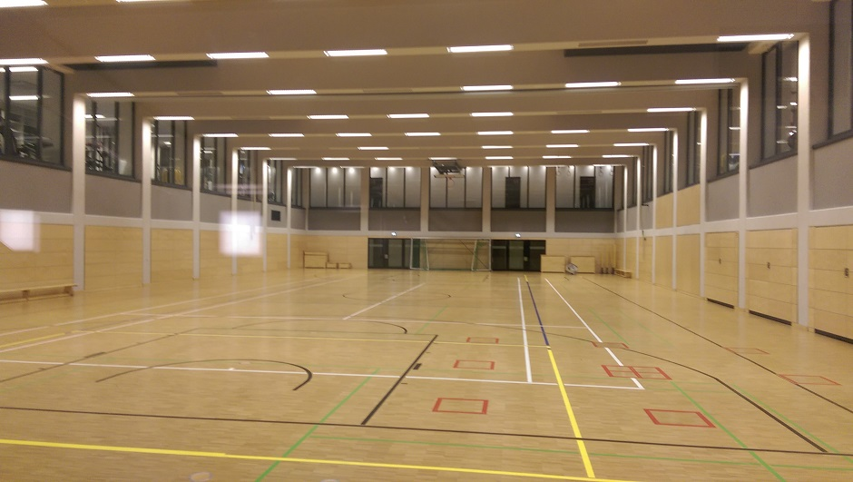 Abgesenkte Sporthalle mit höher gelegenen Krafträumen